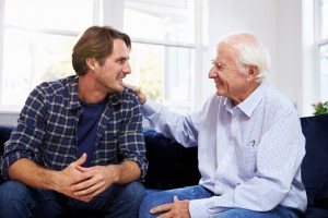 Adult Son Sitting On Sofa And Talking To Father At